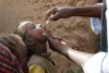 A child receives the polio vaccine from a vaccination team