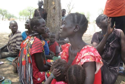 Displaced women and children under a hot sun in South Sudan's Maban County, where food shortages are causing tension.