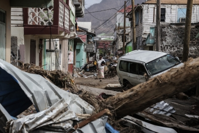 A woman walks in the street of Roseau, capital of Dominica, which is struggling to overcome the severe impact of two category 5 hurricanes which tore through the region in September 2017. P