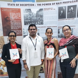Staff and a student from the Institute of International Relations visit the exhibit at the university main library.