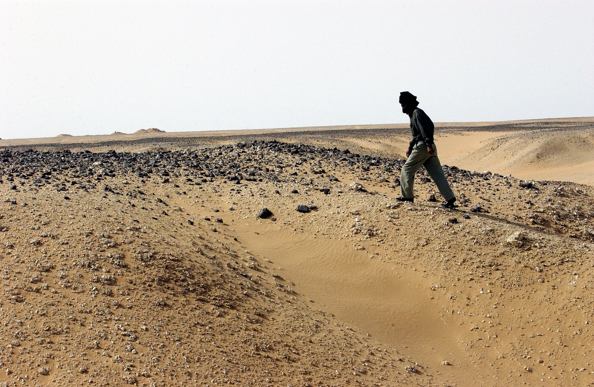 A man walks alone along the desert road between the Dakhla Refugee Camp and Awsaard Refugee Camp