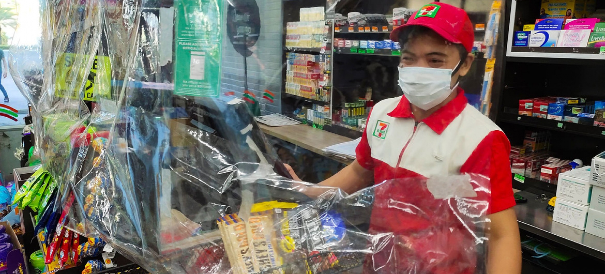 A convenience store requires staff to wear a mask, observe physical distance, and use a plastic sheet barrier as safety measures to prevent the spread of COVID-19, Muntinlupa City, Philippines.