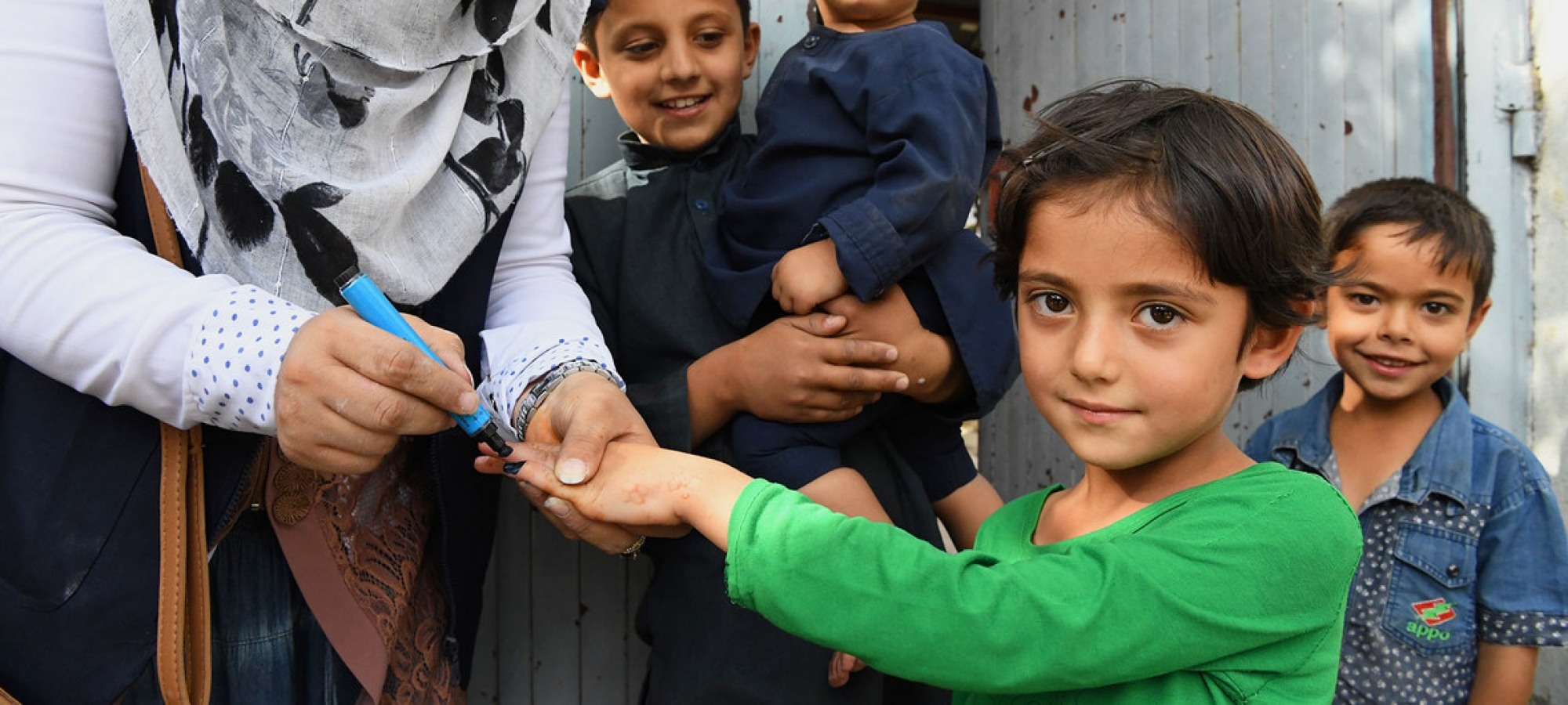 A young girl receives a vaccination against polio from a health worker in Kabul, Afghanistan.