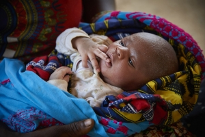 A nine-day-old baby boy is cradled by his mother in Bambaya Village in Fiama Chiefdom, Kono District, Sierra Leone.